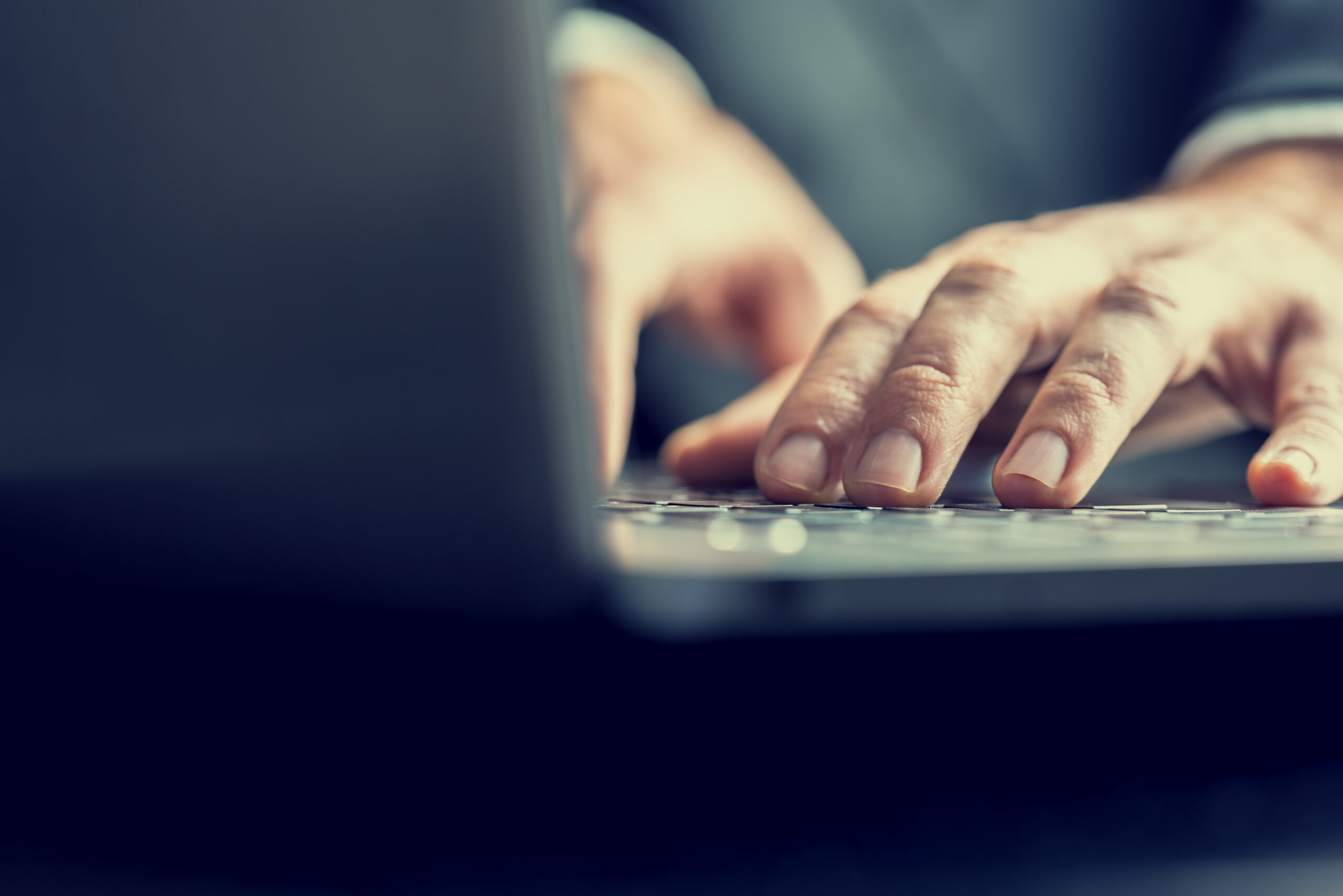 A person's hands working on a laptop